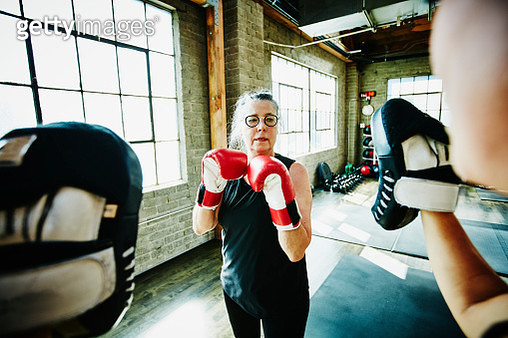 Mature woman boxing with coach in gym - gettyimageskorea