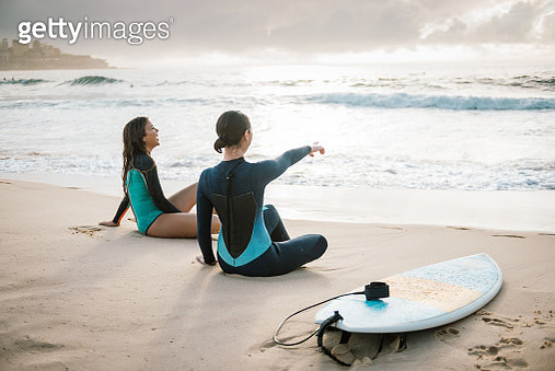 Two young female surfers resting - gettyimageskorea