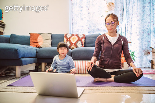 Mom & daughter practising yoga together at home - gettyimageskorea