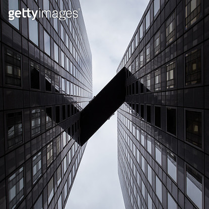 Directly Below Shot Of Elevated Walkway Amidst Office Buildings Against Sky - gettyimageskorea
