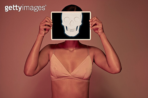Young woman holding tablet in front of face to show skull - gettyimageskorea
