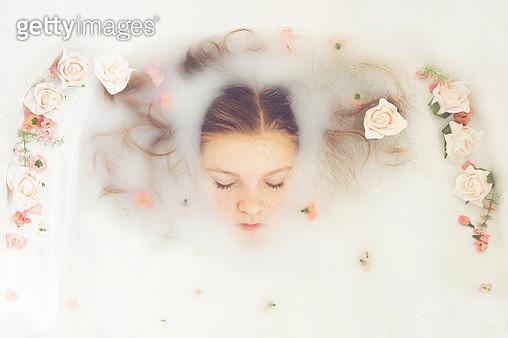 Caucasian teenage girl floating in milk bath with flowers - gettyimageskorea