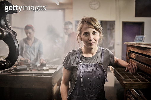 Portrait of female printer looking to camera in busy traditional letterpress studio. - gettyimageskorea