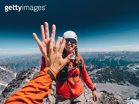 Female mountain climber High Fives her combing partner at the summit - gettyimageskorea
