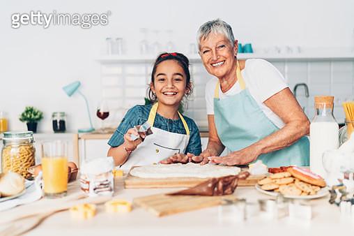 Grandmother and granddaughter preparing cookies together - gettyimageskorea