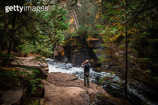 Rear View Of Man Standing By Stream In Forest - gettyimageskorea