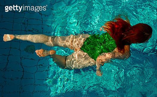 high angle view of woman inside swimming pool relaxing, swimming, wearing green swimwear. - gettyimageskorea