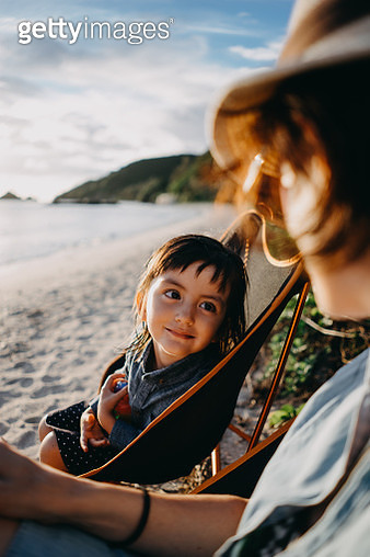 Little girl looking at mother admiringly at beach - gettyimageskorea