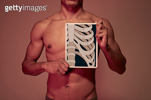 Young man holding tablet in front ofYoung man holding tablet in front of chest to display rib bones - gettyimageskorea
