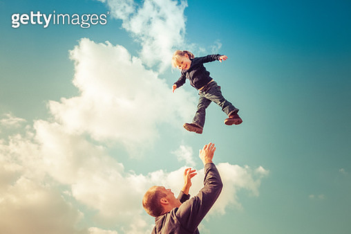 Father catching girl falling from cloudy sky - gettyimageskorea