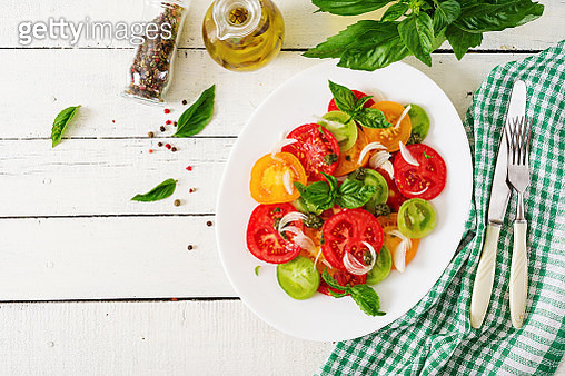 Colored tomato salad with onion and basil pesto. Vegan food. Top view. Flat lay - gettyimageskorea