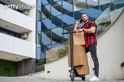 Courier has a lot of boxes to delivery. Courier delivering on electric scooter. - gettyimageskorea