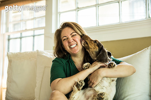 Woman cuddling in bed with dog - gettyimageskorea
