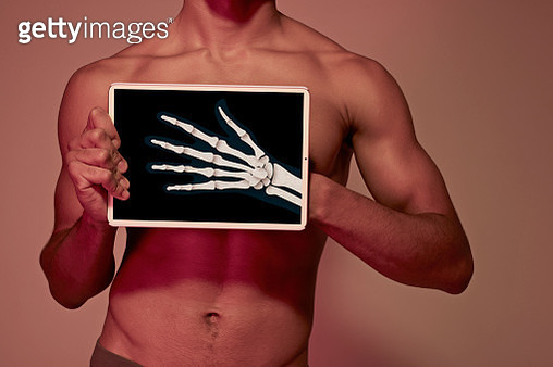 Young man holding tablet in front of body to display hand bones - gettyimageskorea