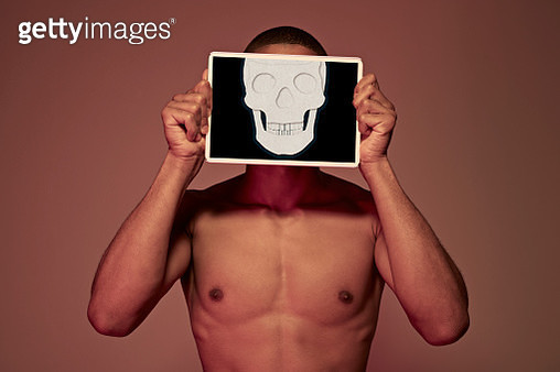 Young man holding tablet in front of face to display skull - gettyimageskorea