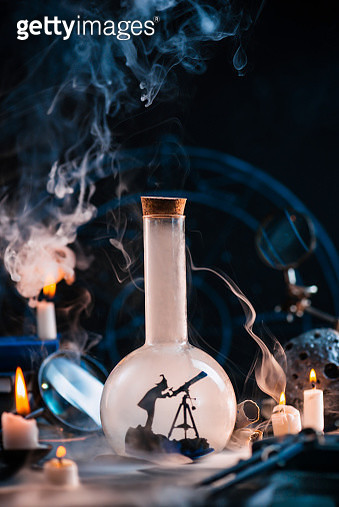 Stargazer silhouette in a laboratory flash on a magical workplace with smoke, candles and meteor. Astrology and astronomy concept with copy space - gettyimageskorea