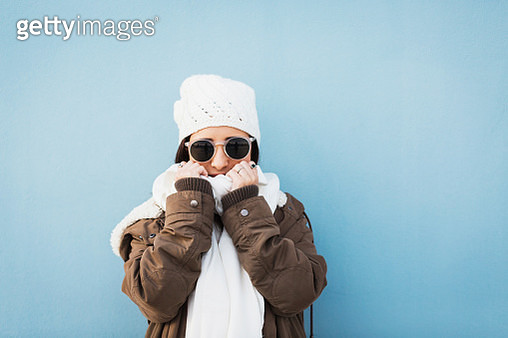 Fashionable woman wearing warm clothing standing against blue background - gettyimageskorea