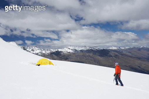 Hiker walking toward tent in snowy mountains - gettyimageskorea