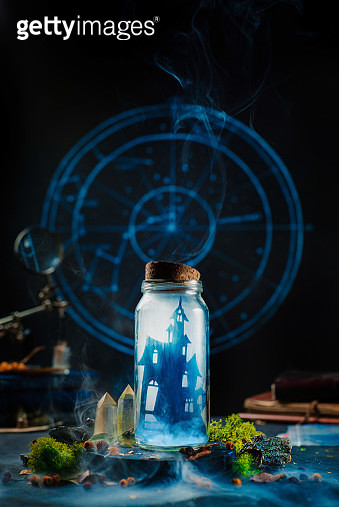 Haunted mansion in a jar with moss, crystals and magical equipment. Starry sty map on a background. Fairy tale book cover concept - gettyimageskorea