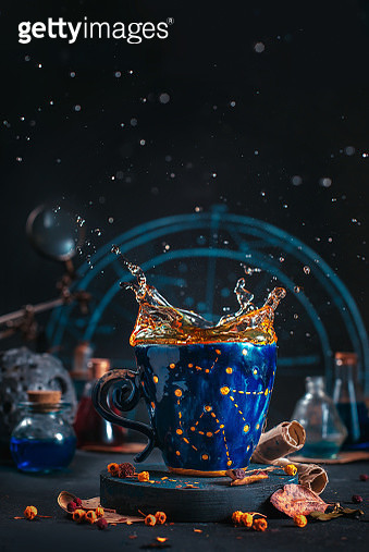 Ceramic cup with golden stars and a tea splash, autumn still life with leaves, berries and tea on a dark background and copy space - gettyimageskorea