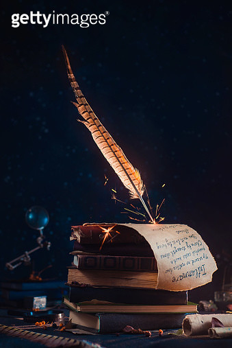 Magical quill with sparks on a top of a stack of books. Wizard spell scroll concept. Fantasy book cover with copy space - gettyimageskorea