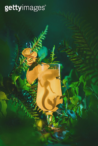 Tall cocktail glass in a tropical scene with a mermaid silhouette inside. Conceptual drink photography with copy space - gettyimageskorea