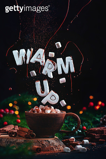 Warm Up text made out of marshmallow flying above a cocoa cup with Christmas decorations, fir tree branches, chocolate and fairy lights. Festive food photography with motion - gettyimageskorea