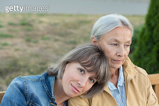 Portrait of mature woman sitting on bench with her mother outdoors - gettyimageskorea