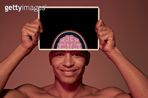 Young man holding tablet in front of head to show brain - gettyimageskorea