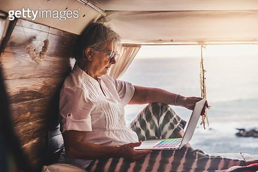 Senior woman sitting in vintage van by he sea, using laptop - gettyimageskorea