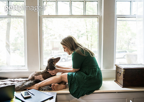 Woman sitting in window with dog - gettyimageskorea