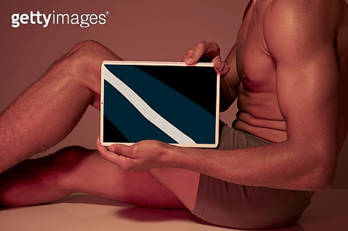 Young man holding tablet in front of body to show leg bone - gettyimageskorea