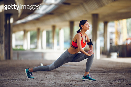 Young woman stretching after jogging in an urban environment - gettyimageskorea