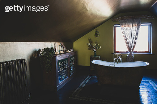 Interior view of attic bathroom with wooden floor, green walls and copper ceiling, freestanding copper slipper bath and vintage cabinet. - gettyimageskorea