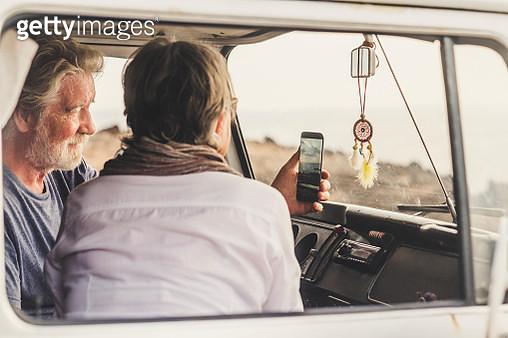 Senior couple traveling in a vintage van, using smartphone - gettyimageskorea