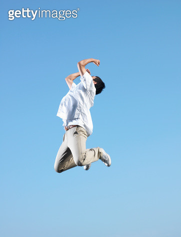 Young man jumping in blue sky - gettyimageskorea