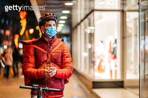 Delivery man with electric scooter using phone - gettyimageskorea