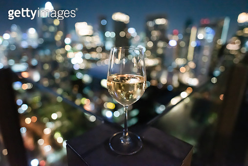 close up view of white wine glass at the rooftop bar with blur bokeh lights at night - gettyimageskorea