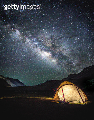 Illuminated Tent Against Mountains At Night - gettyimageskorea