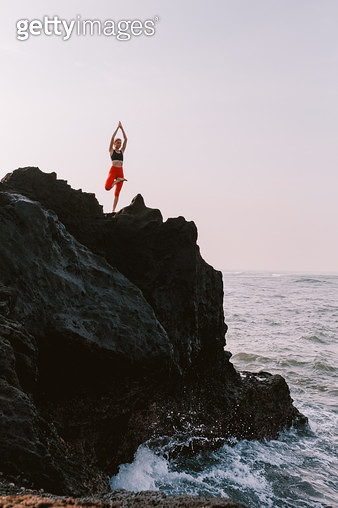 Young woman doing yoga on a rock by the ocean - gettyimageskorea
