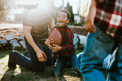 Father Plays Football Outside With His Sons - gettyimageskorea