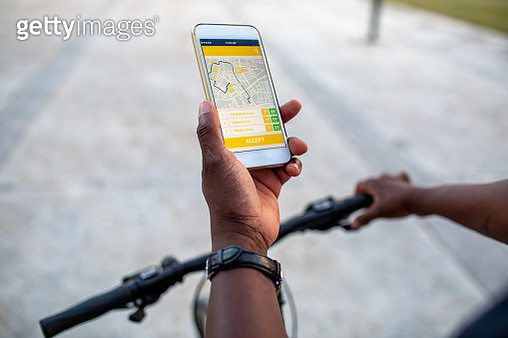 Senior African delivery man using mobile app for delivering food or packages. Close up on hid hands holding smart phone. - gettyimageskorea