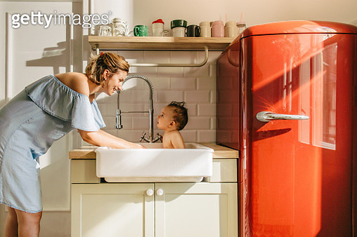 Photo of a baby having a bath in a kitchen sink - gettyimageskorea