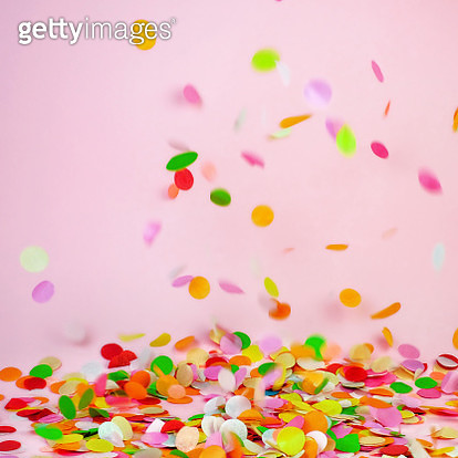 Multicolored falling confetti on a pink background - gettyimageskorea