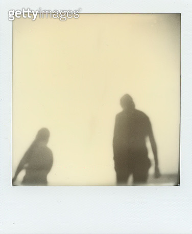 Polaroid photograph of two silhouetted people walking and social distancing - gettyimageskorea