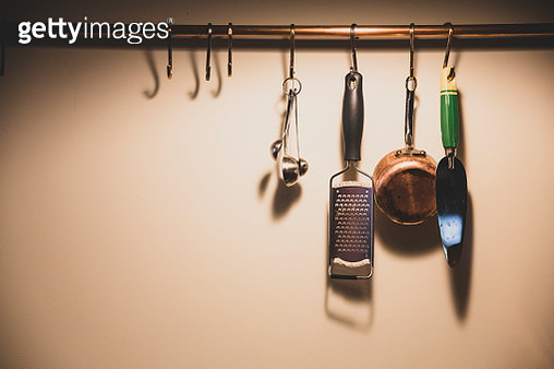 Close up of kitchen utensils suspended from copper pipe. - gettyimageskorea