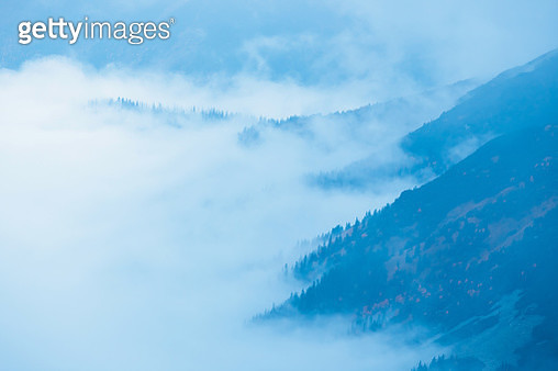Mountain Landscape With Fog Below The Peaks And Clouds Above Them In Blue Tones - gettyimageskorea