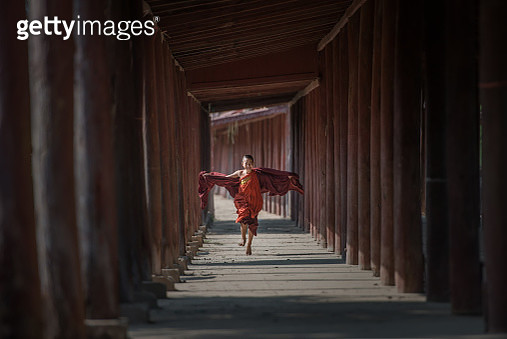 A young monk running with arms outstretched. - gettyimageskorea