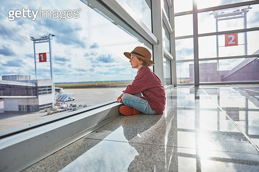 Boy sitting behind windowpane at the airport looking at airfield - gettyimageskorea
