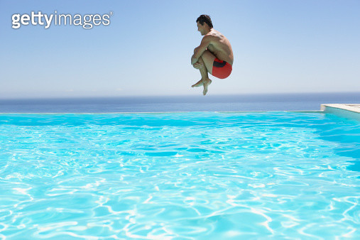 Man leaping into infinity pool - gettyimageskorea